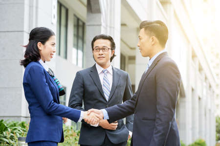 Business partners shaking hands in the city outdoors, they greeting each other before meeting 写真素材