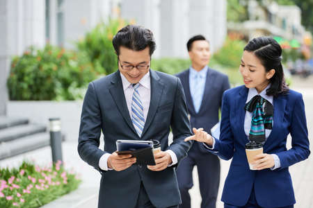 Smiling young businesswoman drinking coffee and discussing online work with her colleague while he using digital tablet outdoors