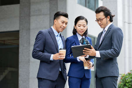 Asian businessman in suit showing online presentation on digital tablet to his colleagues while they standing near the office building outdoors