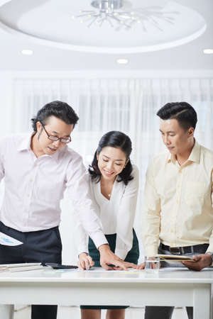 Business people standing near the table examining documents and working in team at office