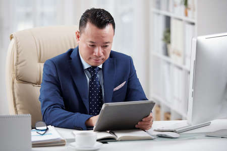 Asian mature businessman sitting at the table at his office and watching something on digital tablet