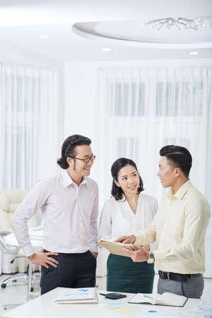 Fiducioso uomo d'affari che spiega alcuni lavori online su tablet digitale ai suoi partner e loro lo ascoltano e sorridono mentre sono in piedi in ufficio