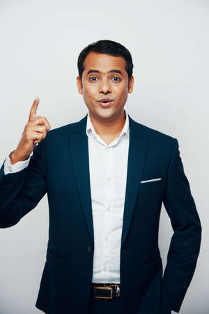 Portrait of Indian young businessman standing in suit and raising his finger up, he has a good idea