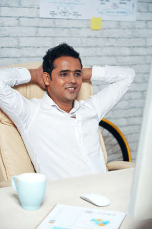 Indian young businessman in white shirt sitting comfortably on chair in front of computer monitor and has a little rest at office 免版税图像