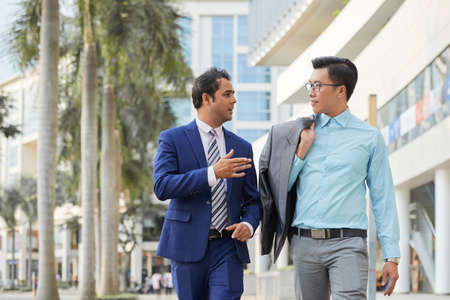 Indian businessman in suit explaining something to his colleague and he listening to him while they walking along the street in the city