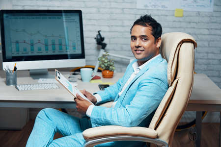 Portrait of Indian young businessman in blue suit sitting on chair and analyzing financial charts on document in his hand and on computer monitor 写真素材