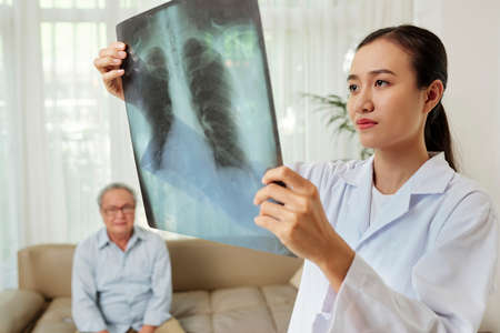 Serious Asian radiologist standing with x-ray image of lungs and examining it with senior man sitting on sofa in the background