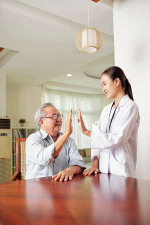 Asian female doctor standing in white coat and giving a high-five to senior man after successful recovery after disease