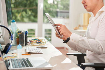 Close-up of young office worker sitting at his workplace and working online on digital tablet at office