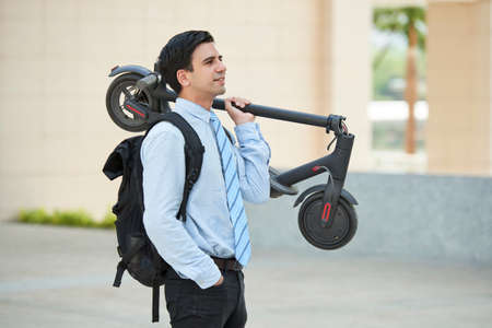 Young handsome businessman with backpack on his back standing with scooter and looking away while riding in the city