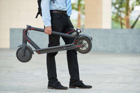 Close-up of businessman holding electric scooter in his hand while standing outdoors in the city