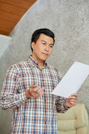 Pensive mature entrepreneur reading document with his speech for conference Stock Photo