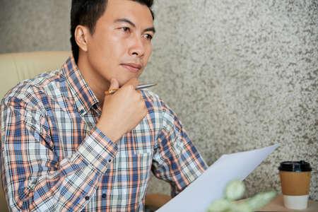 Un entrepreneur vietnamien mature réfléchit à deux fois avant de signer un contrat