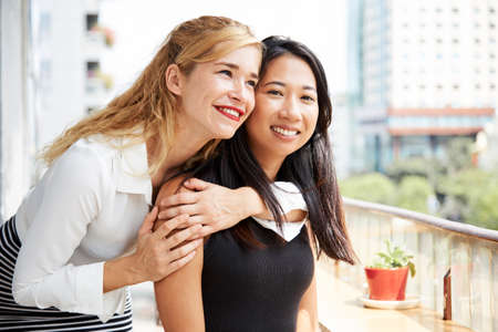 Portrait of happy beautiful young woman hugging her best friend Stock Photo