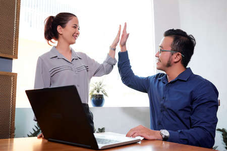 Happy Vietnaemse business colleagues giving each other high five to express unity Imagens