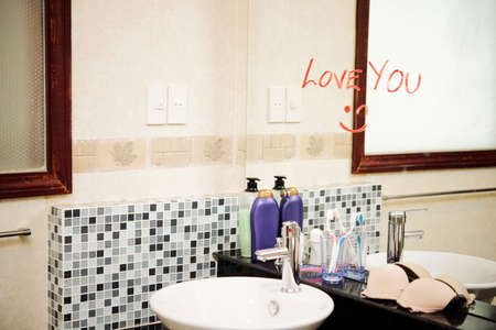 Love message written with red lipstick on the mirror in the modern bathroom 免版税图像
