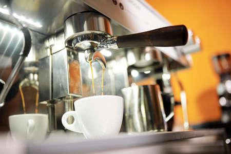Nahaufnahme des Prozesses der Herstellung von Cappuccino mit Kaffeemaschine im Café