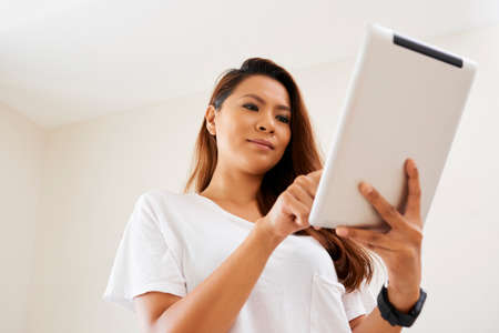 Asian young woman standing and communicating online on digital tablet 版權商用圖片