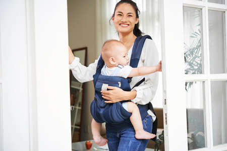 Happy young beautiful mixed-race woman carrying baby boy in sling when opening front door of her house Stock Photo