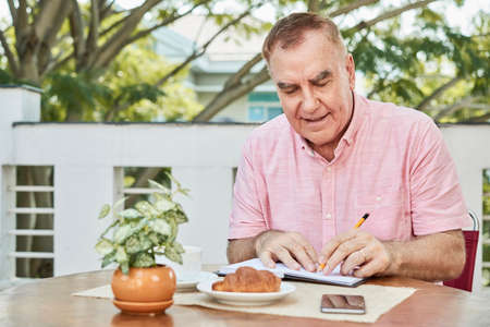 Positive aged man sitting at table in outdoor cafe and writing in planner