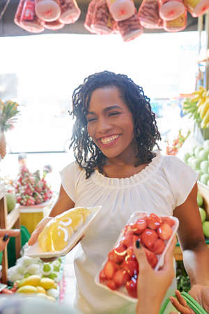 Cheerful young Black woman buying fruits and barries at local market