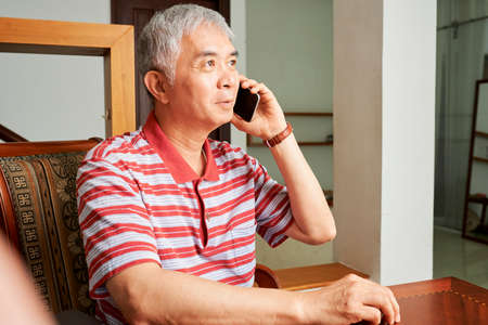 Asian senior man wearing striped casual clothing sitting at the table and listening to somebody on mobile phone at home Imagens