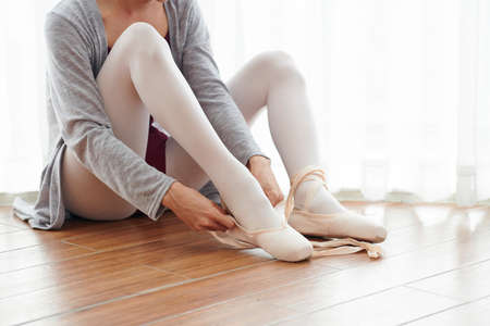 Close-up of young ballet dancer sitting on the floor wearing pointe shoes on her feet and is going to dance ballet in school
