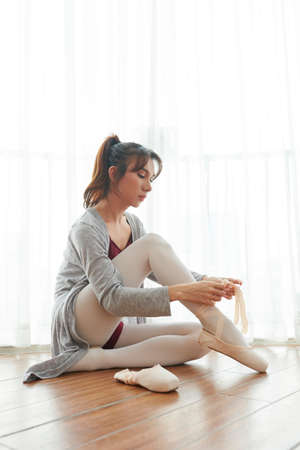 Young ballet dancer sitting on the floor wearing pointe shoes before training in dance studio