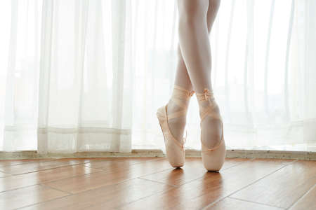 Close-up of graceful ballet dancer standing on pointe shoes on wooden floor during training in ballet class