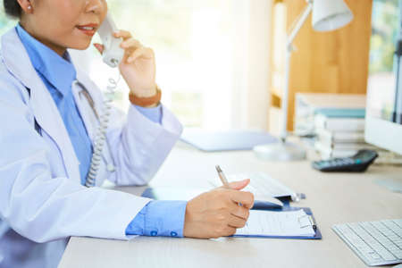 Close-up of young female doctor in white coat sitting at the table writing a prescription in document while talking on the phone at office
