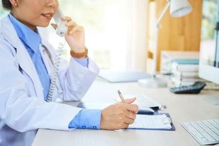 Gros plan sur une jeune femme médecin en blouse blanche assise à la table en train d'écrire une ordonnance dans un document tout en parlant au téléphone au bureau Banque d'images