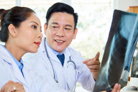 Asian male radiologist pointing at x-ray image in his hands and consulting with female doctor during their work at hospital Foto de archivo