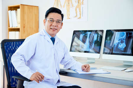 Portrait of Asian male doctor sitting in white coat at the table in front of computer monitors with x-ray images and looking at camera