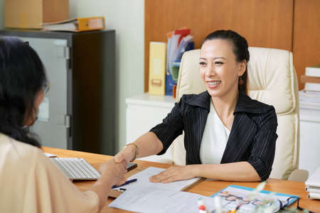 Smiling Asian businesswoman sitting at her workplace and shaking hands to client they working in team and concluding a deal Imagens - 124630862