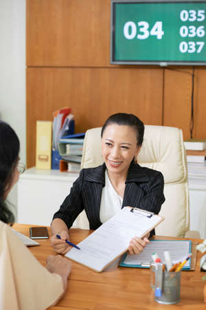 Asian young social worker smiling to her client and pointing at business contract and suggesting her to conclude a deal Stock Photo