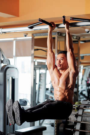 Muscular Asian man breathing out when raining core muscles and doing hanging leg rises 版權商用圖片