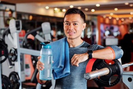 Portrait of positive Vietnamese sportsman standing in gym with water bottle and towel on his shoulder 스톡 콘텐츠