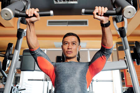 Fit handsome Asian man concentrated on doing chest exercises exercise on fly machine Stock Photo