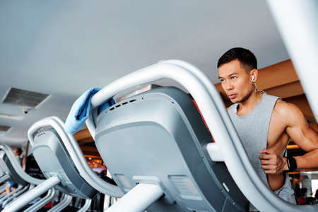 Serious young Asian man listening to music in earphones when running on treadmill