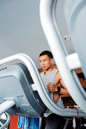 Determined fit young Vietnamese man jogging on treadmill in gym in the morning