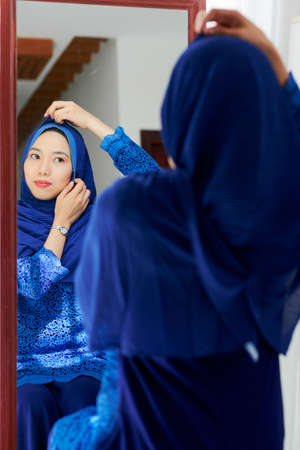 Young smiling Muslim woman putting on traditional headwear in front of mirror Stock Photo