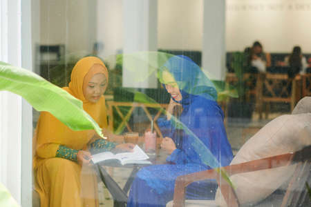 Muslim female students sitting at cafe table and reading book together