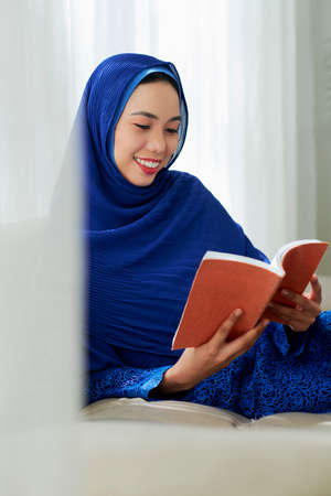 Young Vietnamese Muslim woman in traditional dress reading book at home