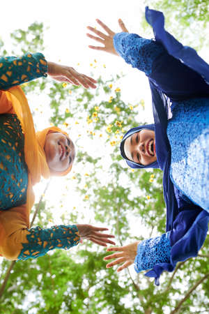 Happy excited young Asian muslim women throwing flower petals in the air and looking at camera, view from below