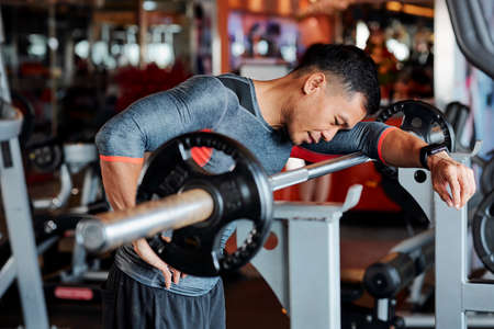 Tired young Vietnamese man standing at workout bench and leaning on barbell after doing exercise Imagens - 124875145