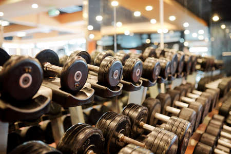 Rows of metal dumbbells on rack for strength training in gym Imagens - 124875159