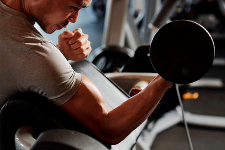 Close-up of Asian young bodybuilder sitting and ldoing exercise with dumbbell in gym Stock Photo