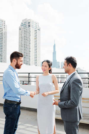 Asian young businesswoman smiling and shaking hands with businessman during their meeting outdoor in the city