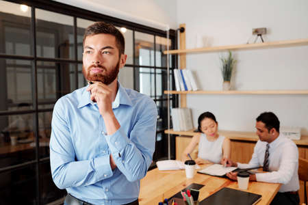 Young bearded businessman standing at office and thinking over something with his partners sitting at the table and working together in the background