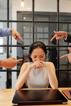 Asian young manager sitting at her workplace with laptop with a guilty look with business people pointing at her and blame her